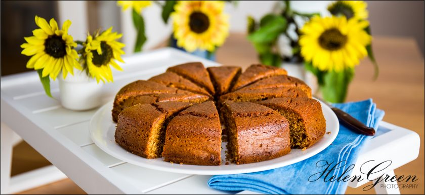 Ginger, rum and lime cake with sunflowers in the background by Helen Green Photography