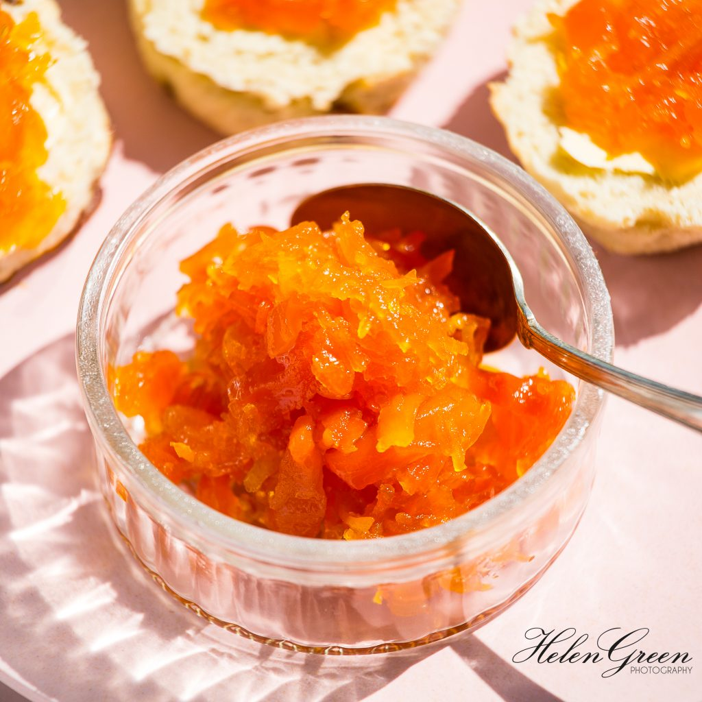 carrot marmalade in a small jar on a pink plate with 3 scones