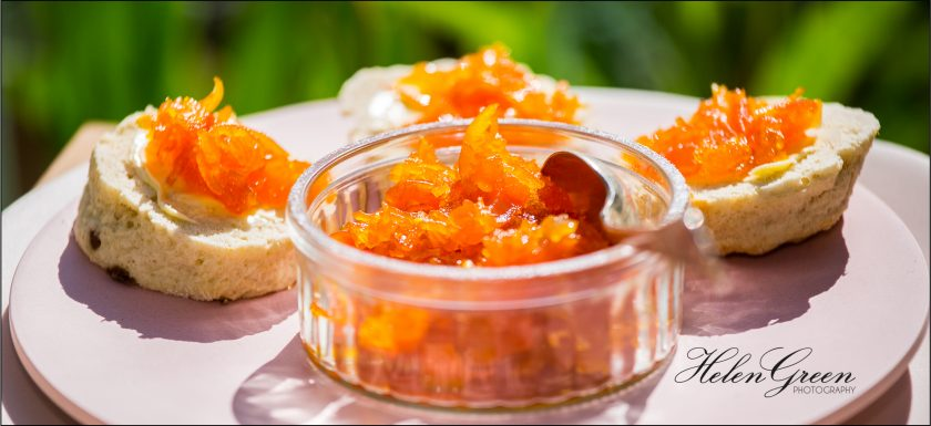 small jar of carrot marmalade with 3 scones with carrot marmalade on and green background