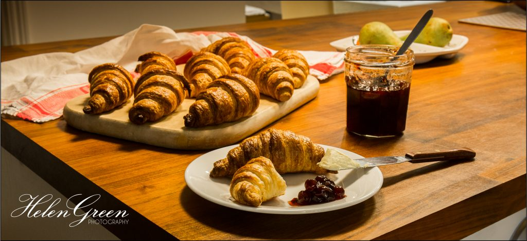 A croissant with jam on a plate in front of a bread board with lots of croissants